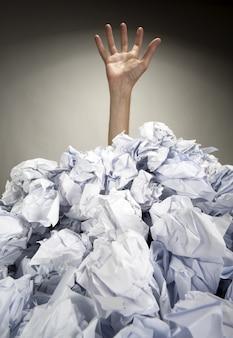 Mão se estende de uma pilha de papéis