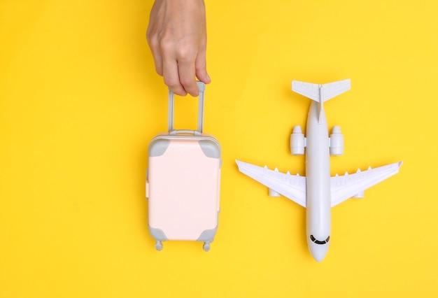 Mão segura a bagagem de viagem do mini fantoche e o avião em fundo amarelo. tempo de viagem. vista do topo