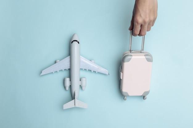 Mão segura a bagagem de viagem do mini fantoche e o avião sobre fundo azul. tempo de viagem. vista do topo