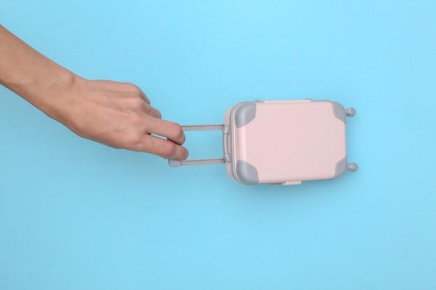 Mão segura a bagagem de viagem do mini fantoche sobre um fundo azul. tempo de viagem
