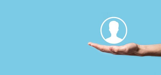 Mão segura a interface de ícone de pessoa do usuário em fundo azul. símbolo de usuário para o design de seu site da web, logotipo, app, ui.banner.