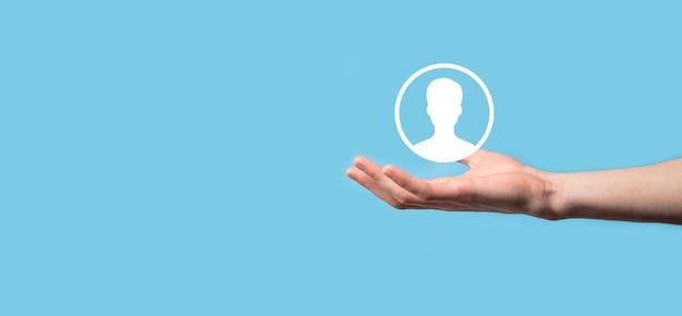 Mão segura a interface do ícone da pessoa do usuário na superfície azul