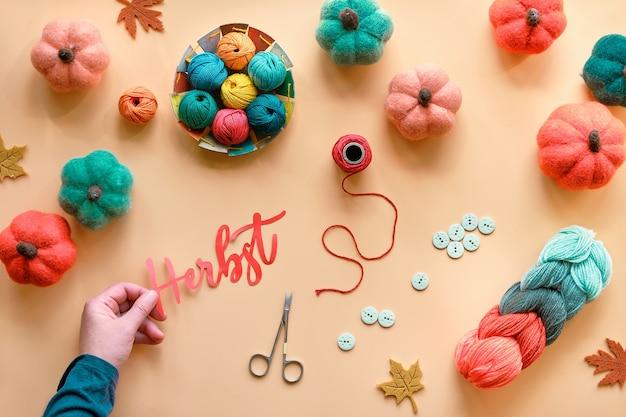 Mão segura a palavra danke feita de papel. significa obrigado em alemão. materiais de artesanato em cores do outono, laranja, verde. fundo de outono com abóboras de feltro, lã e suprimentos.