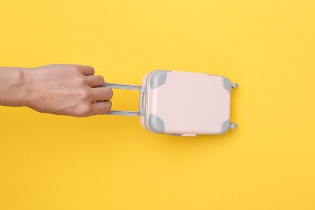 Mão segura bagagem de viagem de mini fantoche em fundo amarelo. tempo de viagem