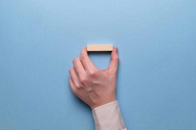Mão segura blocos de madeira em um espaço azul.