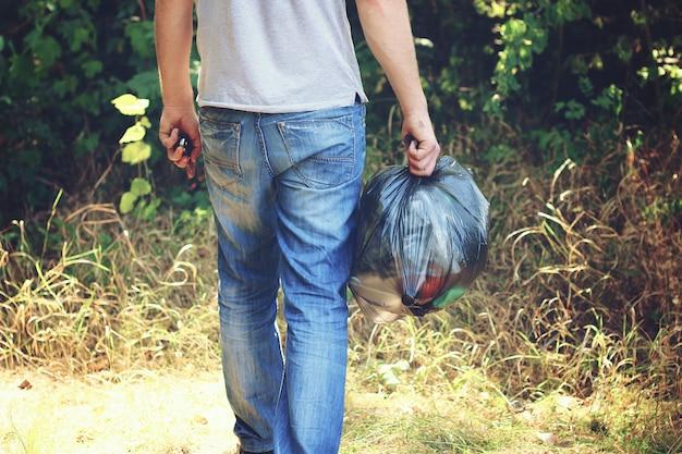 Mão segura contra uma floresta cheia de lixo um grande saco de plástico preto, um dia de verão