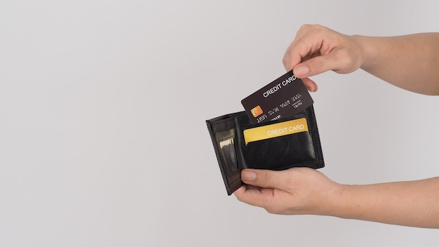 Mão segura o cartão de crédito preto e a cor dourada na carteira preta, isolada no fundo branco.