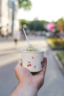 Mão segura o copo de papel com sorvete