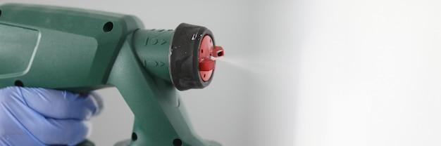 Mão segura o equipamento de spray de tinta na parede