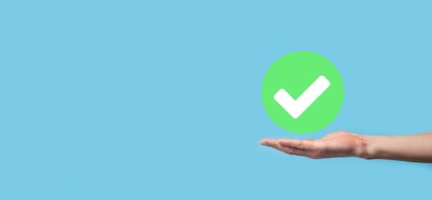 Mão segura o ícone verde, marca de seleção, sinal de marca de seleção, ícone de carrapato, sinal da direita, botão de marca de seleção verde do círculo, done.on fundo escuro. banner.copy space.place for text.