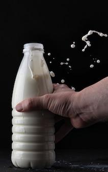 Mão segura o leite em uma garrafa em um fundo preto com um splash