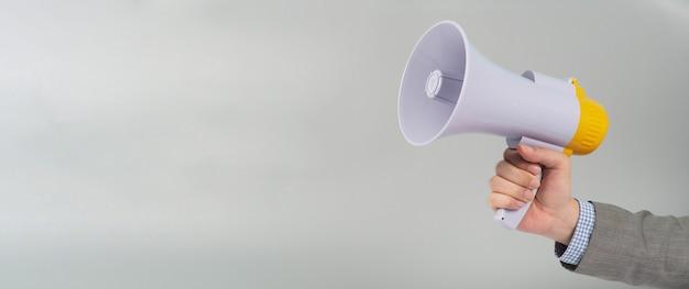 Mão segura o megafone e usa um terno cinza sobre fundo cinza.