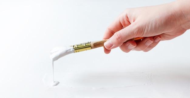 Mão segura o pincel e pinta a superfície branca