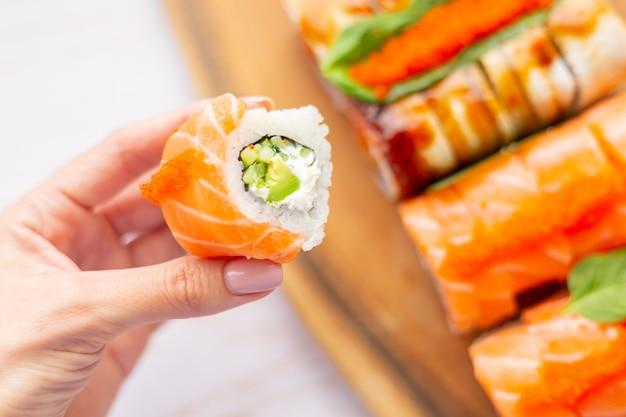 Mão segura o rolo com salmão e cream cheese