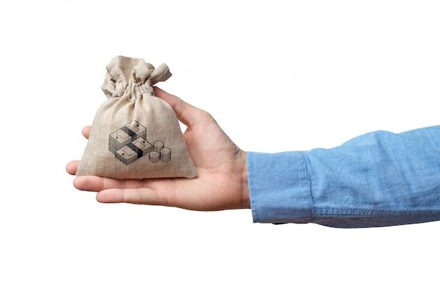 Mão segura o saco de pano com o ícone de dinheiro em fundo branco.