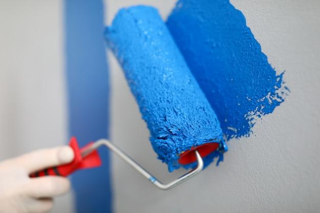 Mão segura rolo e fio na parede com tinta azul