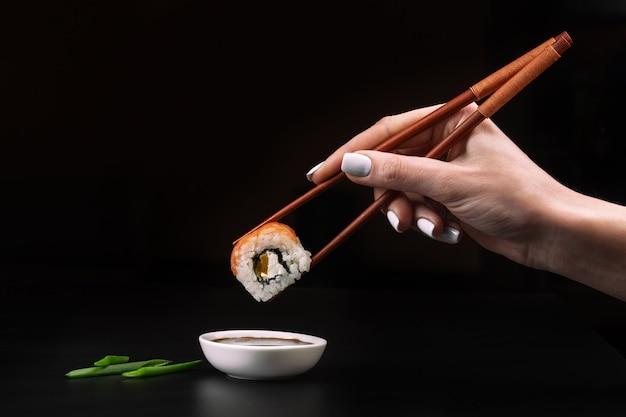 Mão segura sushi sobre a tigela com molho de soja na mesa preta.
