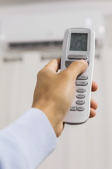 Mão segura um controle remoto do ar condicionado