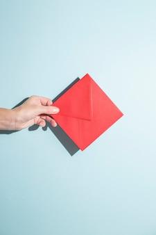 Mão segura um envelope em um fundo azul. sombras duras.