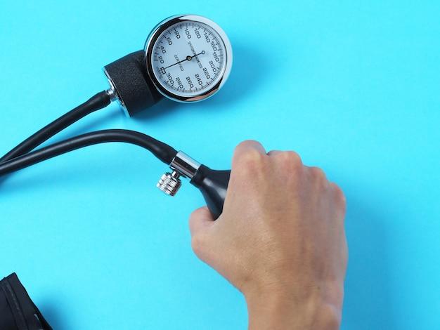 Mão segura um monitor de pressão arterial que mostra a pressão arterial