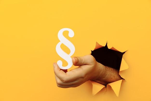Mão segura um parágrafo como um sinal de justiça e lei através de um buraco de papel amarelo
