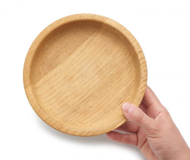 Mão segura um prato de madeira marrom vazio em um fundo branco e isolado