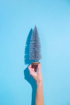 Mão segura uma árvore de natal decorativa em um fundo azul. bandeira.