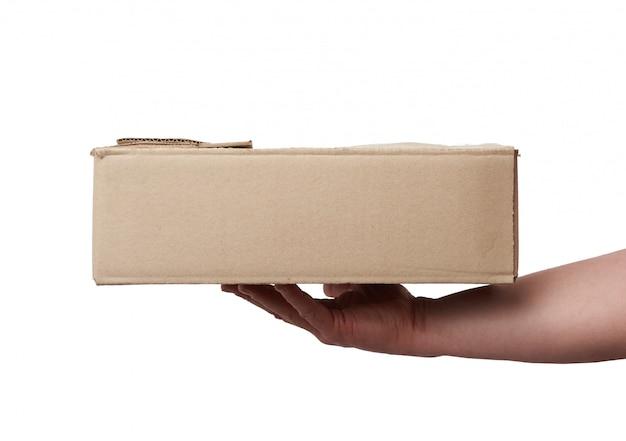 Mão segura uma caixa de papelão marrom de papel em um branco isolado