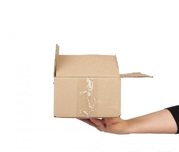 Mão segura uma caixa de papelão marrom de papel