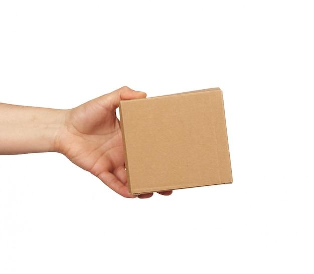 Mão segura uma caixa de papelão marrom sobre uma superfície branca isolada