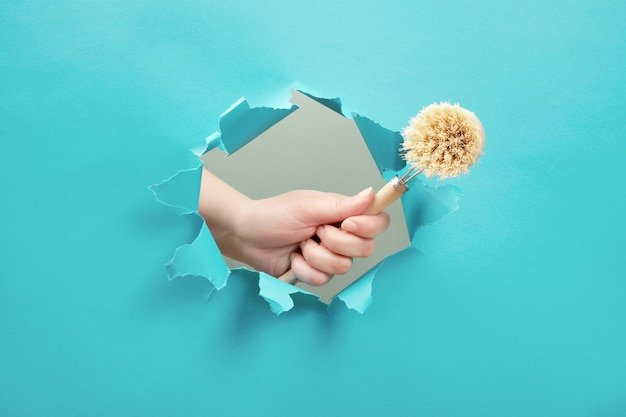 Mão segura uma escova de lavar louça através de um buraco de papel