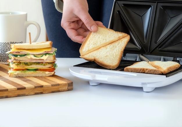 Mão segura uma fatia de pão frita da toster perto de sanduíche fresco cozido com queijo, bacon e vegetais.