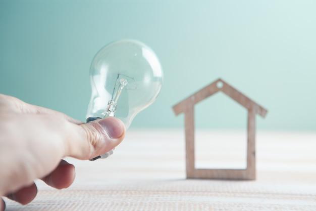 Mão segura uma lâmpada e uma pequena casa