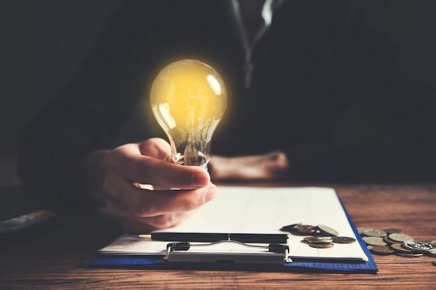 Mão segura uma lâmpada sobre uma prancheta