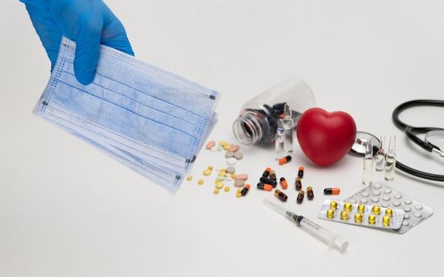 Mão segura uma máscara médica contra um fundo de um coração de brinquedo vermelho e pílulas proteção contra o coronavírus