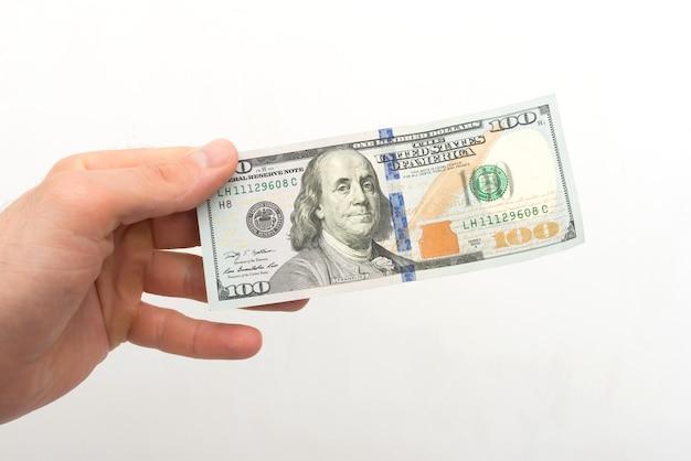Mão segura uma nota de 100 dólares em uma superfície branca