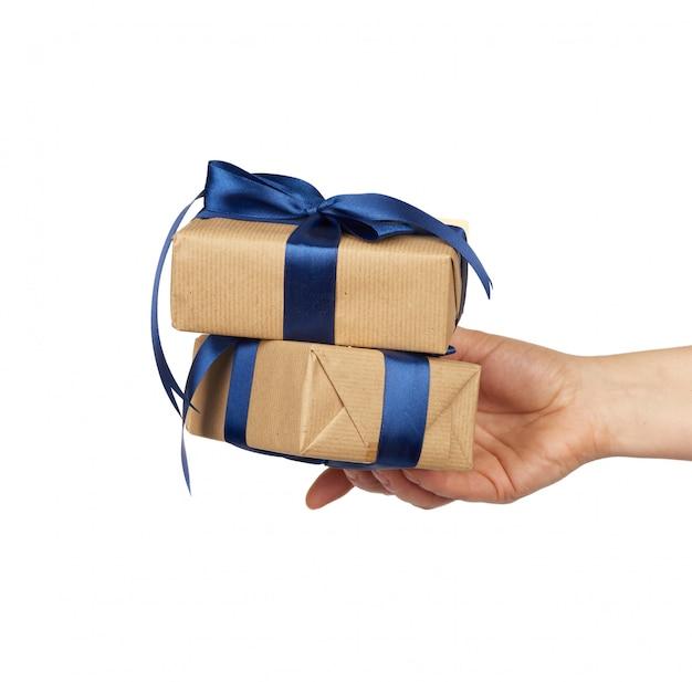 Mão segura uma pilha de presentes embrulhados em papel artesanal marrom com laços de seda amarrados