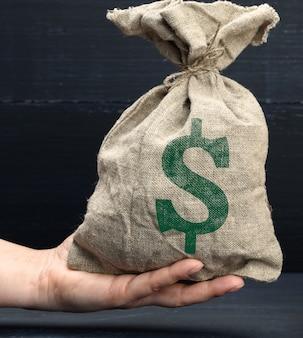 Mão segura uma sacola de lona cheia de dinheiro com o ícone de um dólar americano em uma superfície azul