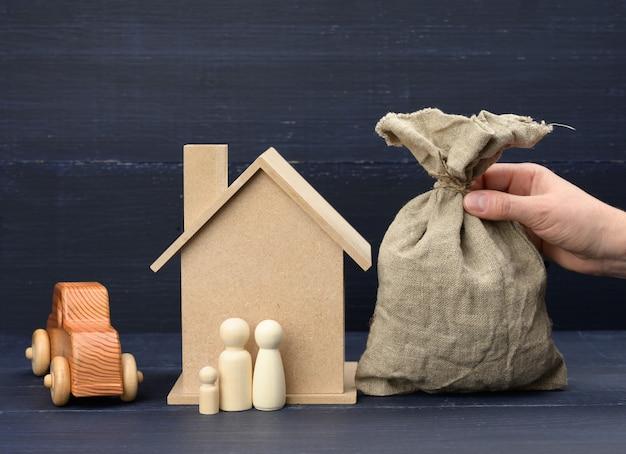 Mão segura uma sacola de lona cheia de dinheiro e uma casa de madeira em uma superfície azul