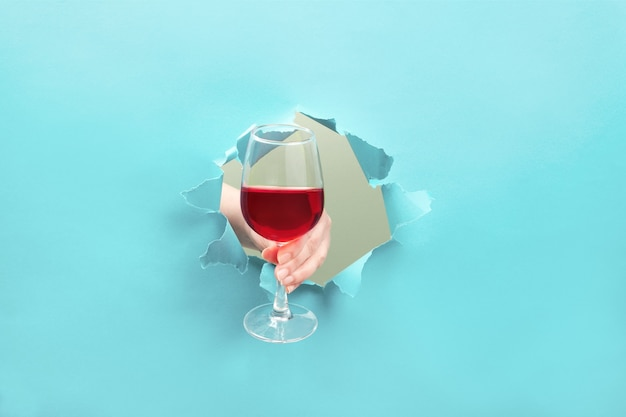 Mão segura uma taça de vinho tinto por um buraco rasgado.