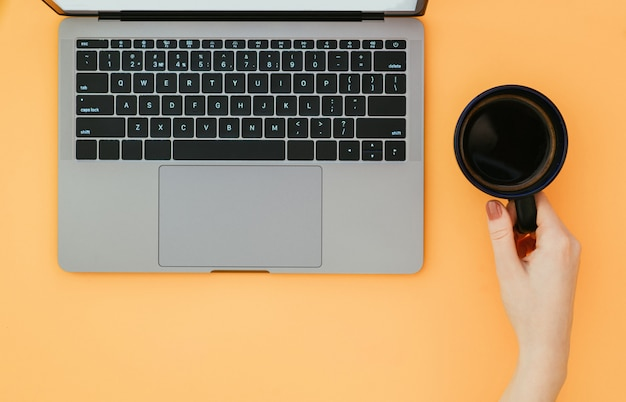 Mão segura uma xícara de café e um laptop em uma superfície laranja