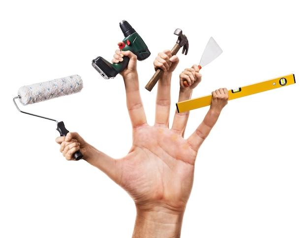 Mão segura várias ferramentas de construção isoladas no trabalhador manual do conceito de fundo branco