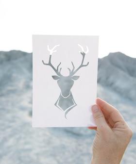Mão segurando a arte de alce de papel perfurada com fundo de montanha