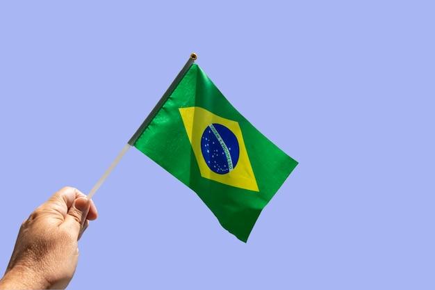 Mão segurando a bandeira brasileira com o fundo do céu. bandeira do brasil. ordem e progresso em português.