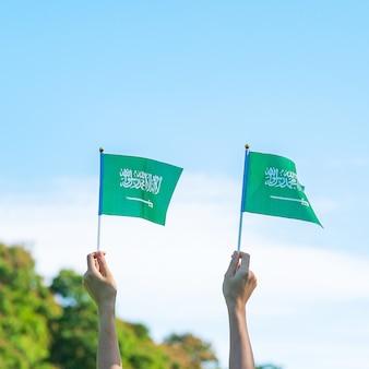 Mão segurando a bandeira da arábia saudita no fundo do céu azul. dia nacional da arábia saudita de setembro e conceitos de celebração feliz