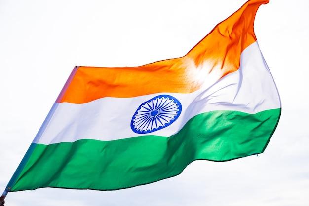 Mão segurando a bandeira da índia sobre o fundo do céu azul. dia da independência da índia, 15 de agosto.