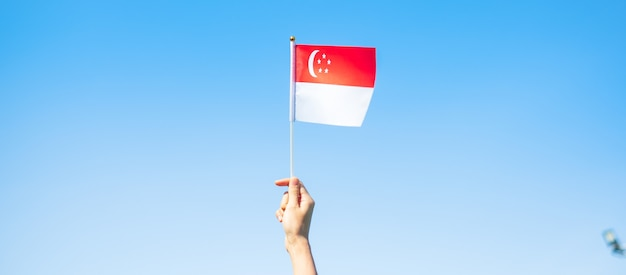 Mão segurando a bandeira de singapura no fundo do céu azul. dia nacional de cingapura e conceitos de celebração feliz
