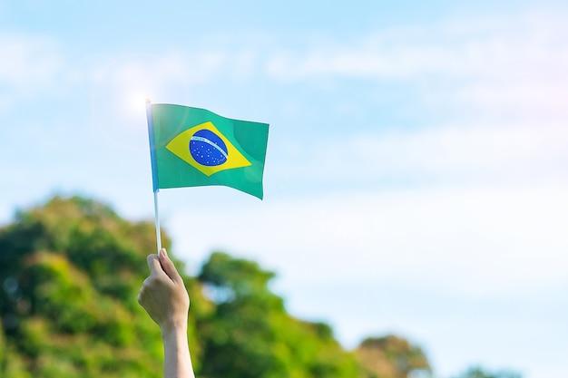 Mão segurando a bandeira do brasil no fundo do céu azul. conceitos de dia da independência de setembro e celebração feliz
