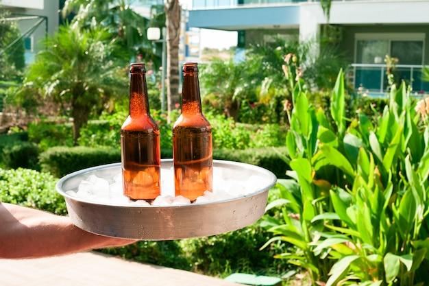 Mão segurando a bandeja com garrafas de gelo e cerveja