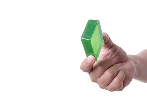 Mão segurando a barra de sabão artesanal verde feita à base de plantas